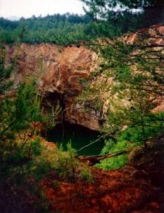 dark-green water-filled sinkhole with surrounding red-colored rock formations and pine forests